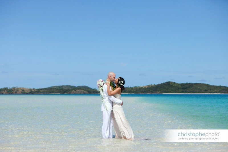 Bride and groom posing in the pristine clear water of the island directed by wedding photographer fiji.
