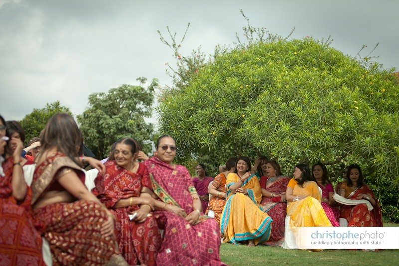 Group of women resting in the shade during an outdoor ceremony.