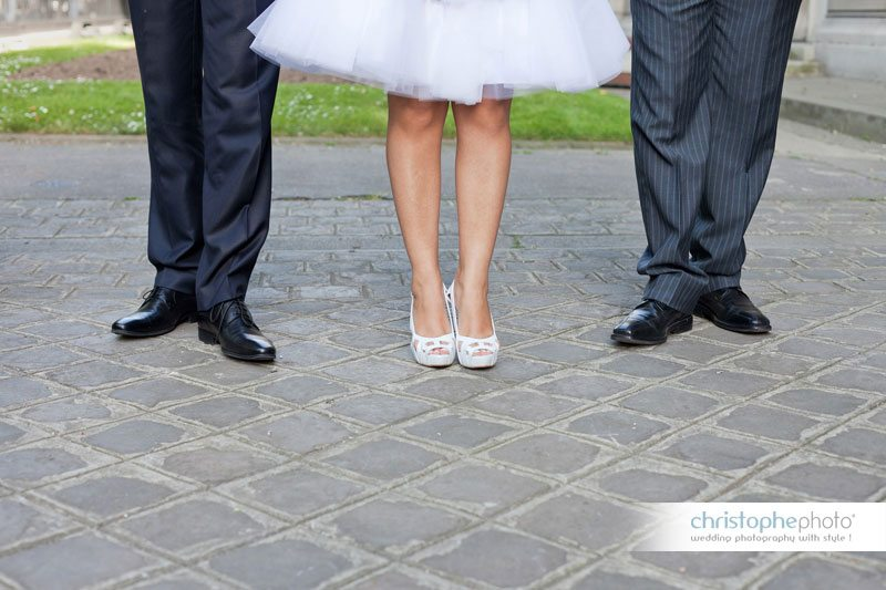 The wedding dress is like a ballerina dress. The bride is sourrounded by her husband and his brother.