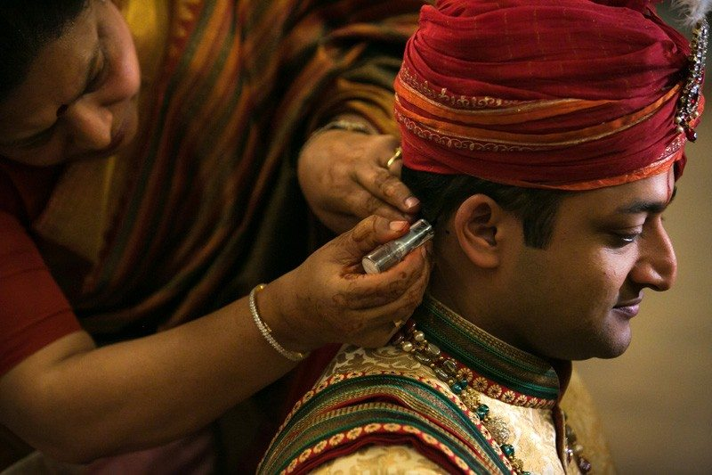 A traditional custom where the groom is getting perfume behind his hear in preparation of the wedding ceremony.